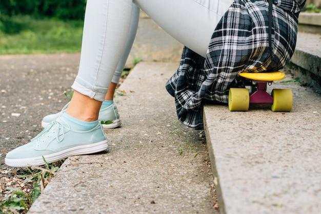 Meisjeszitting op een skateboard in het park