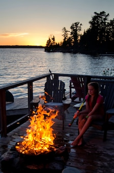 Meisjeszitting op een stoel dichtbij een kampvuur, meer van het hout, ontario, canada