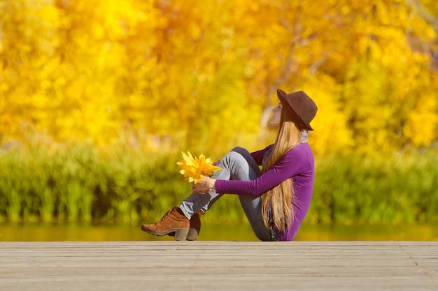 Meisjeszitting op het dok met de herfstbladeren in handen