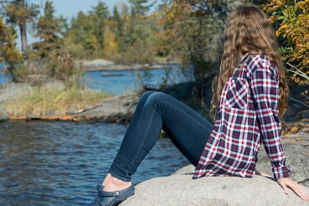 Meisjeszitting op rots bij oever van het meer, meer van het hout, ontario, canada