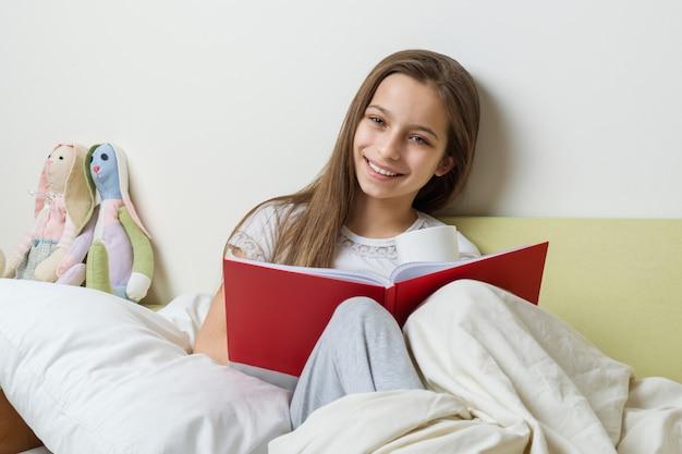 Meisjeszitting thuis in bed met een schoolnotitieboekje