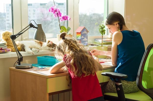 Meisjeszussen thuis aan de tafel schilderen met waterverf