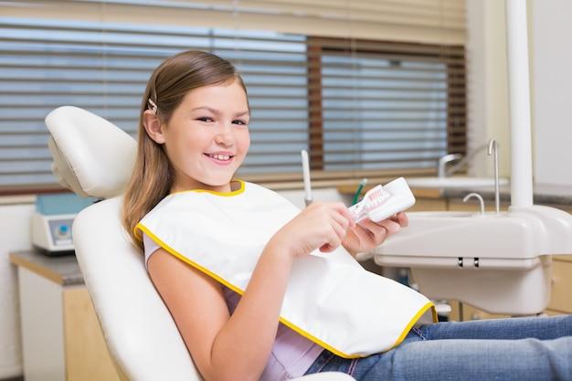 Meisjezitting als tandartsenvoorzitter die modeltanden bekijken