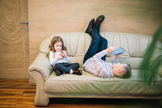 Meisjezitting dichtbij zijn broer die digitale tablet op bank thuis bekijken