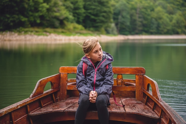 Meisjezitting in een houten boot