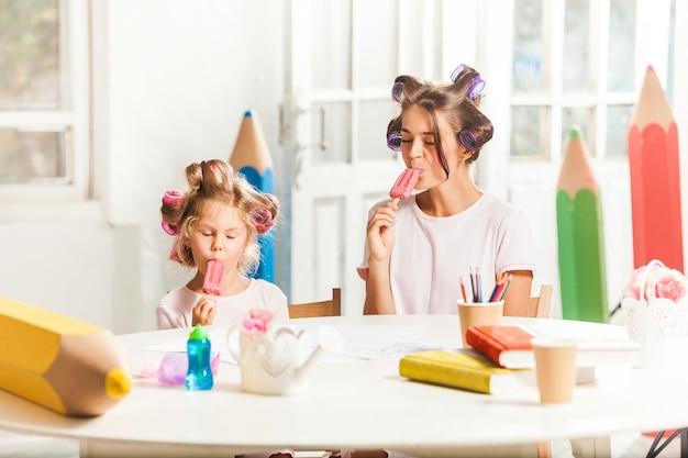 Meisjezitting met haar moeder en het eten van roomijs