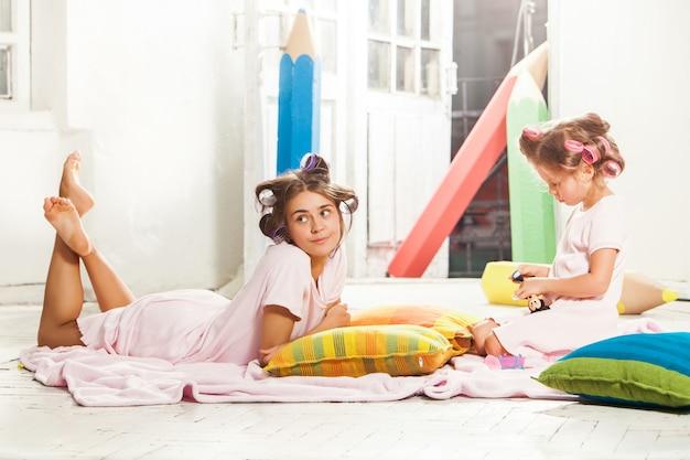 Meisjezitting met haar moeder en het spelen