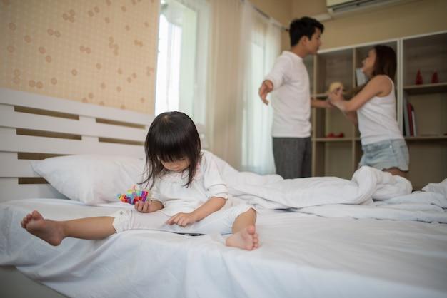 Meisjezitting met haar ouders op het bed dat ernstig kijkt