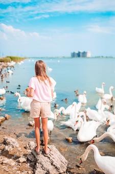 Meisjezitting op het strand met zwanen en voedend hen