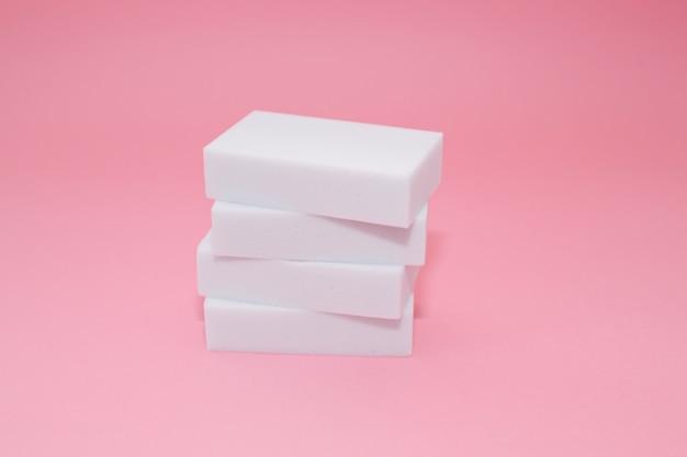 Melamine huishoudensponsstapel met vier sponsen voor het schoonmaken op roze achtergrond.