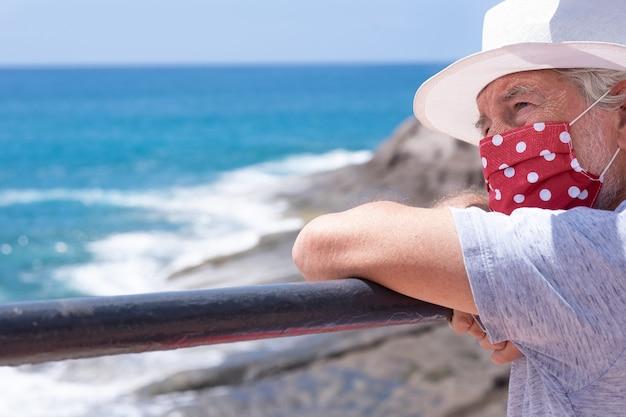 Melancholische bejaarde man zit bij de zee met een beschermend masker vanwege het coronavirus blauwe zee