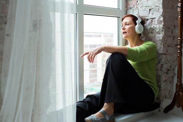 Melancholische senior vrouw luisteren muziek