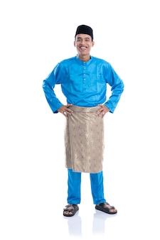 Melayu mannetje met satijnen kleren die zijn hand op heupen over witte achtergrond glimlachen