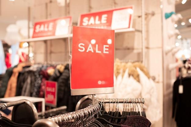 Meld u met de inscriptie verkoop in kledingwinkel en een plek voor een inscriptie