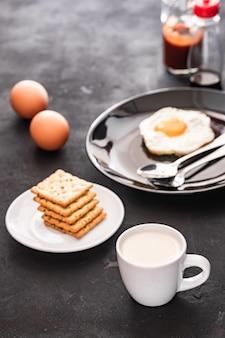 Melk beker serveren met cracker en gebakken ei bij het ontbijt