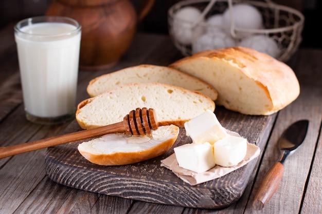 Melk, boter, eieren en vers brood op een houten tafel. ontbijtproducten.