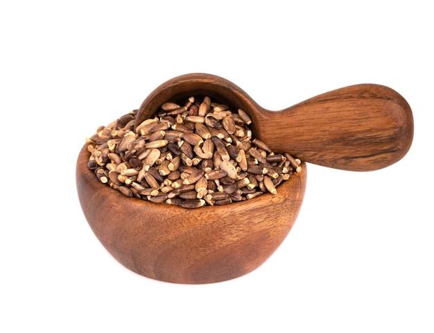 Melk distel zaad in houten kom en lepel, geïsoleerd op een witte achtergrond.