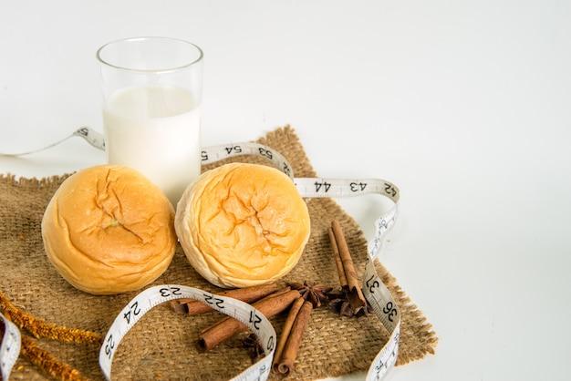 Melk en brood met meetlint voor dieet op witte achtergrond