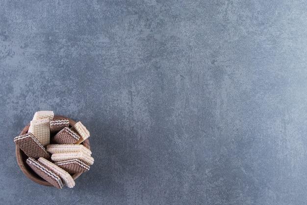 Melk en chocoladewafeltjes in een kom, op de marmeren achtergrond.
