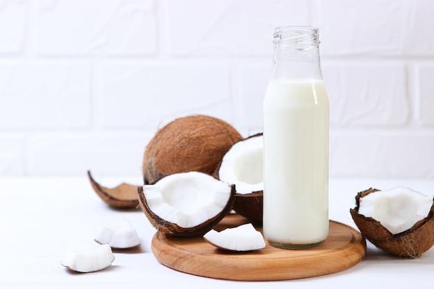 Melk en gebroken kokosnoten op tafel plantaardige melk een vega drankje
