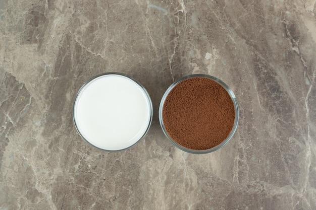 Melk en gemalen koffie op marmeren tafel