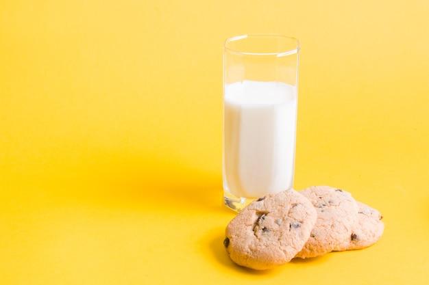Melk en koekjes op gele achtergrondexemplaarruimte