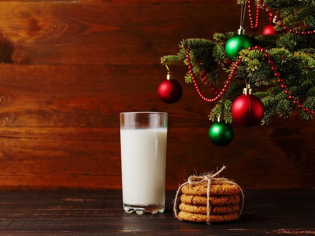Melk en koekjes voor de kerstman onder de kerstboom. , copyspace.