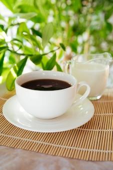Melk en koffiekop op bamboemat