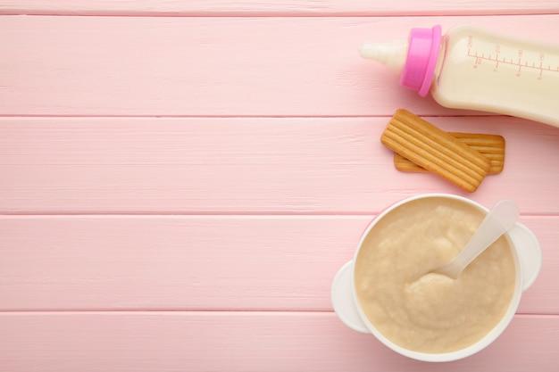Melk en kom met pap voor baby op roze ondergrond