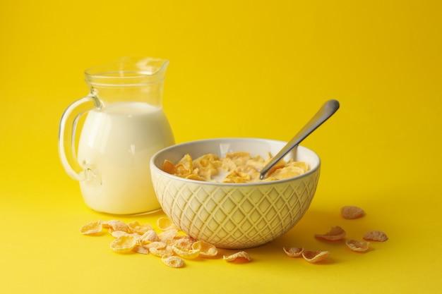 Melk en kom muesli op gele achtergrond