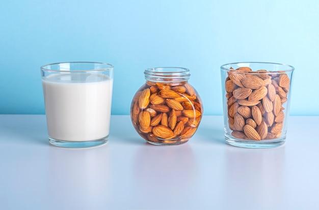 Melk en noten op en een glas en een pot op blauwe achtergrond