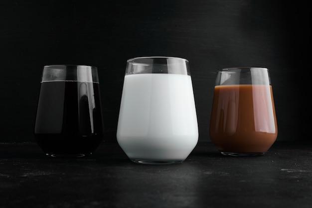 Melk, espresso en warme chocolademelk in glazen bekers.