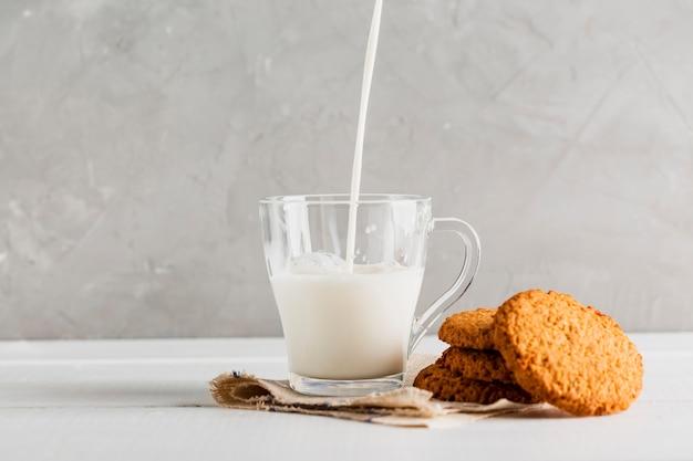 Melk gegoten in glas met koekjes