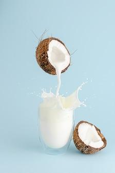 Melk gieten van een kokosnoot en splash in een glas op pastel blauwe achtergrond. voedsel levitatie concept. verticaal