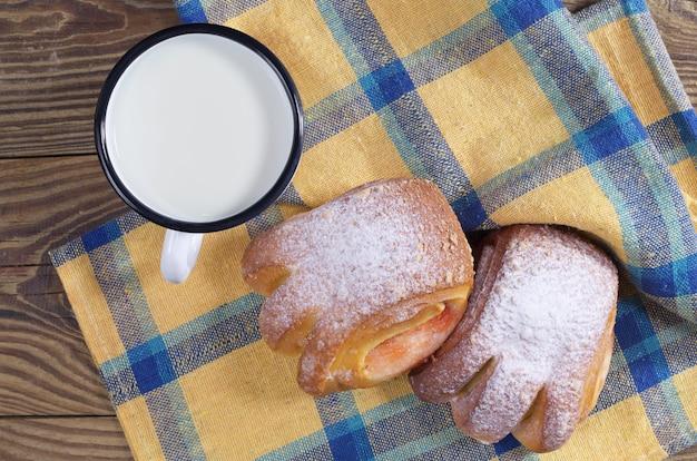 Melk in een emaille mok met zoete broodjes op tafel