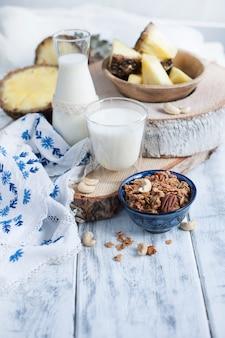 Melk in een glas en in een fles, muesli in een blauwe kop en ananas en tafelkleed met blauwe bloemen