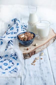 Melk in een glas en in een fles, muesli in een blauwe kop met tafelkleed met blauwe bloemen