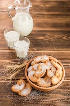 Melk in een glas en in een kruik in de buurt van de plaat van cookies op tafel