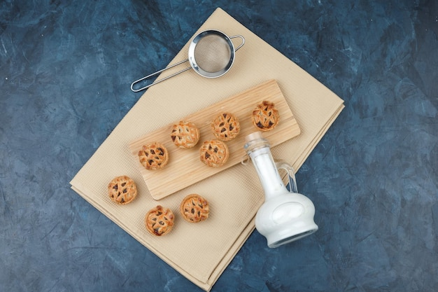 Melk in een kan met stuk zak, textiel, vergiet en chocoladekoekjes