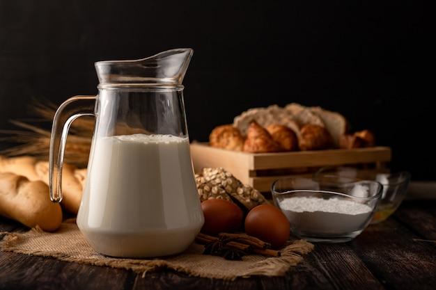 Melk in een kruik die op een houten lijst met ingrediënten wordt geplaatst