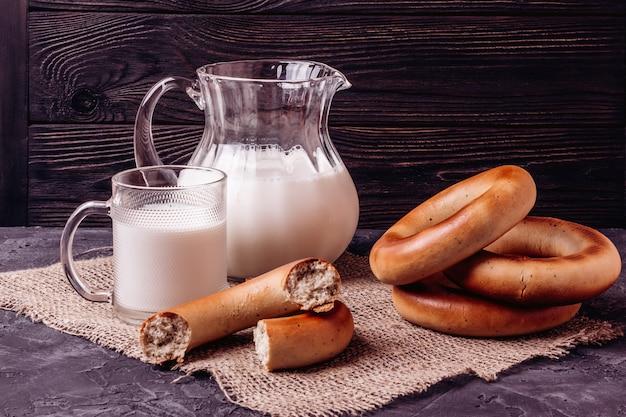 Melk in een kruik en kopjes en bagels op een tafel