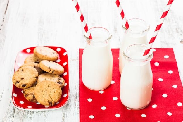 Melk in fles met papieren rietje met koekjes