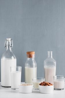 Melk in flessen en glazen met haver en amandelen