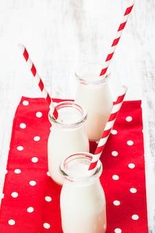 Melk in flessen met papieren rietjes voor kinderen op het rode stippen servet