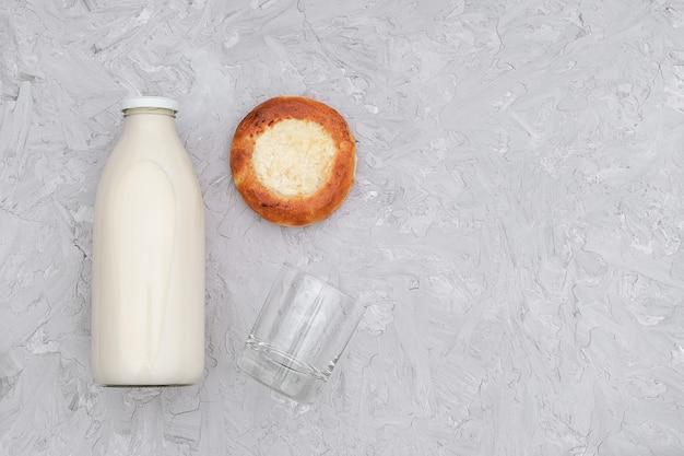 Melk in glazen fles, één leeg glas en vers gebakken broodje op grijs