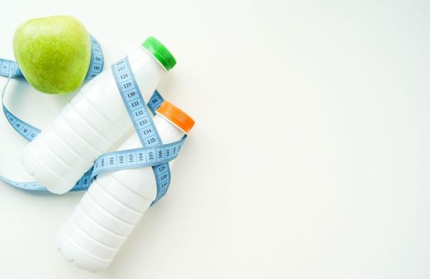 Melk, kefir, water met meet- of centimetersband op witte achtergrond