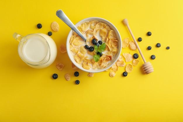 Melk, kom muesli en beer op gele achtergrond