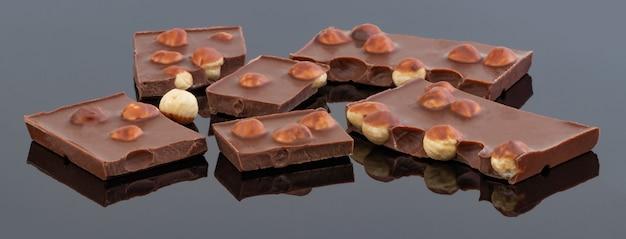 Melk of pure chocolade met noten op zwarte achtergrond.