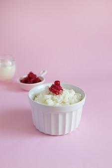 Melk rijst pap met bevroren bessen op roze achtergrond met kopie ruimte