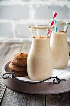 Melk vanille smoothies met havermoutkoekjes in glazen potten op het oude houten oppervlak. selectieve aandacht.